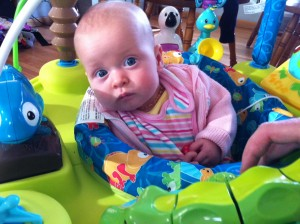 Holding her hands, Ella Mae was unsure of the exersaucer....