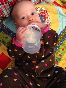 Ella Mae can hold her own bottle of milk.